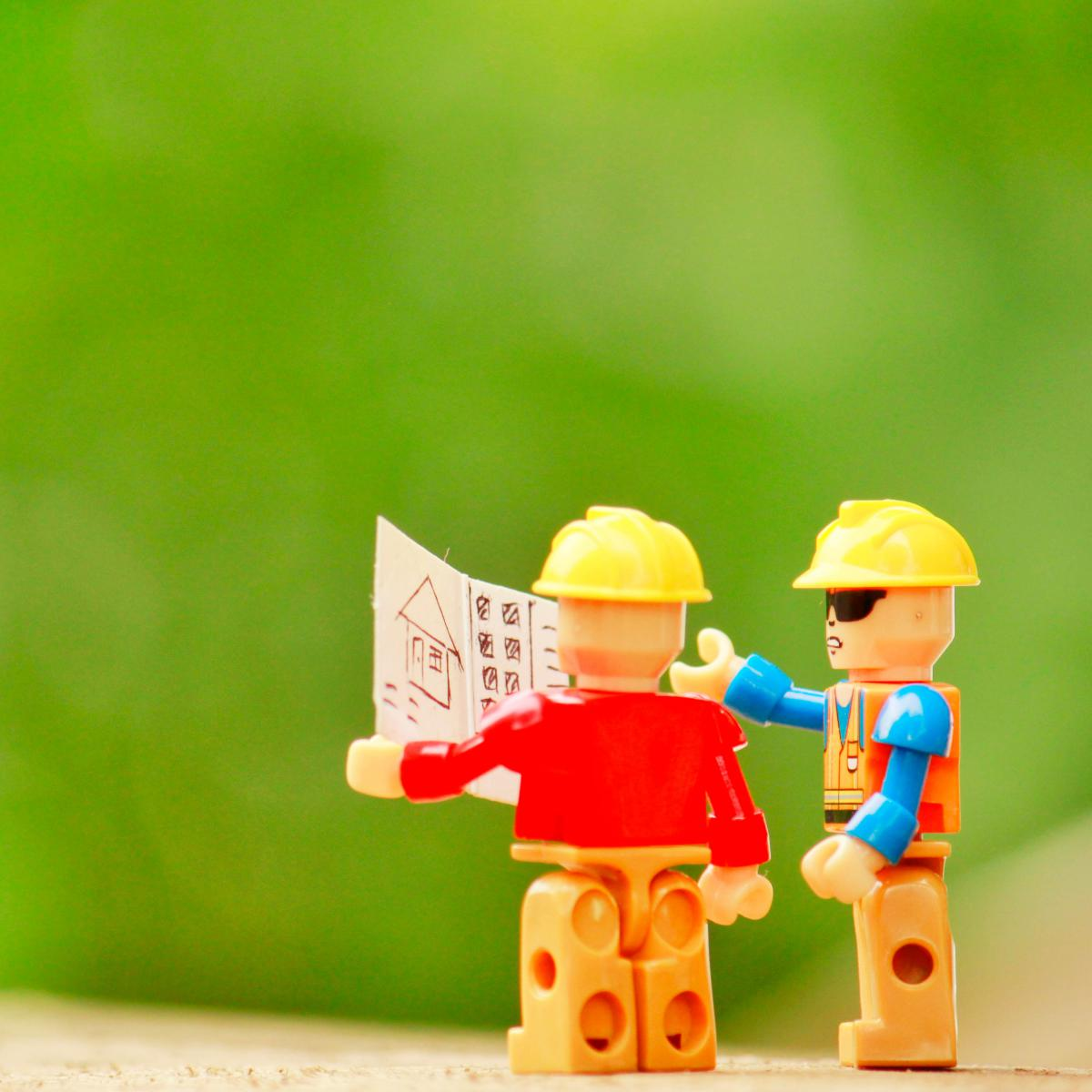 two lego men looking at a piece of paper